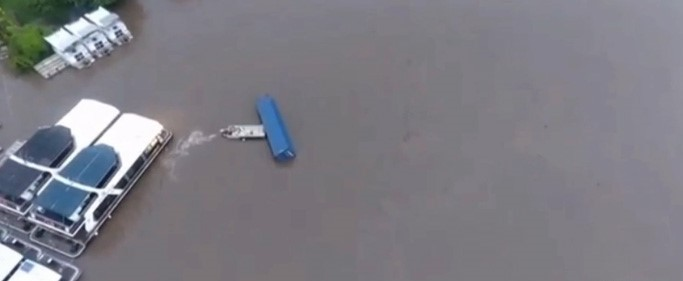 Drone Shows Man Saving Houseboats From Being Crushed By A Shipping Container